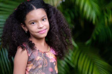 Portrait of a cute multiracial small girl with a green vegetation background