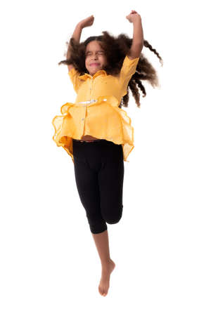 Multiracial small girl jumping with her eyes closed and a funny expression- Isolated on a white background Standard-Bild