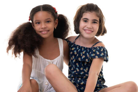 Two friendly small girls, friends or sisters - Hispanic and african-american - Isolated on white Banco de Imagens