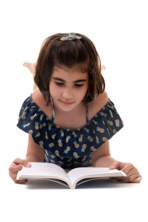Cute hispanic small girl laying on the floor and reading a book - Isolated on a white background