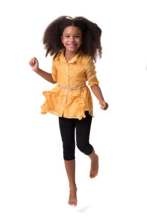 Happy multiracial small girl jumping or running and laughing - Isolated on white Standard-Bild