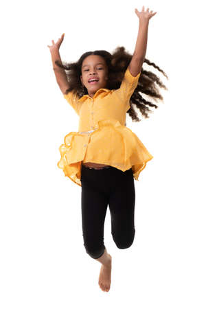 Happy multiracial small girl jumping in the air and laughing - Isolated on white Standard-Bild