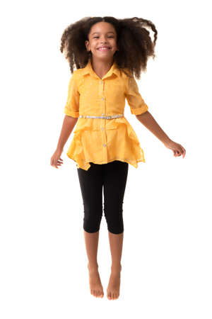 Cute multiracial small girl jumping and laughing - Isolated on a white background
