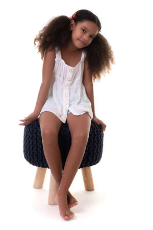 Cute multiracial small girl sitting on a stool seat - Isolated on a white background