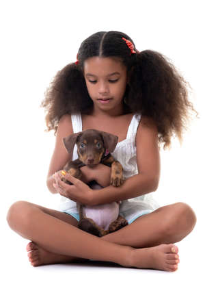 Adorable multiracial girl holding a small stray dog - Isolated on a white background Standard-Bild