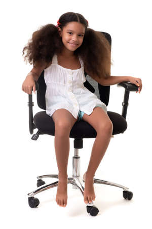 Cute multiracial small girl sitting on an office chair - Isolated on a white background Standard-Bild