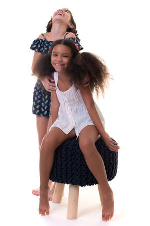 Two friendly small girls laughing , friends or sisters  - Hispanic and african-american - Isolated on white Standard-Bild