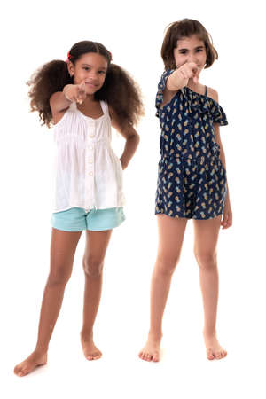 Two small girls pointing at the camera  - Hispanic and african-american - Isolated on white