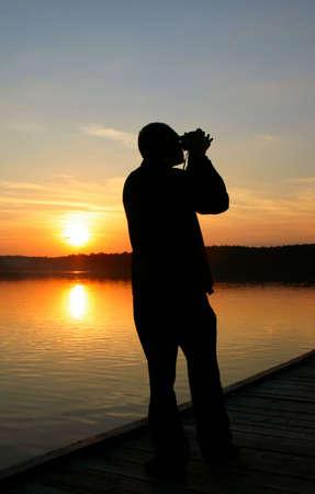 murk: photographer capturing sunset Stock Photo