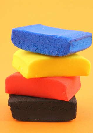 playdoh: pile of colorful plasticine blocks on orange background