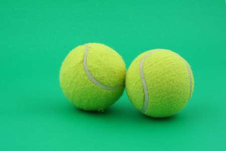two tennis balls on green photo