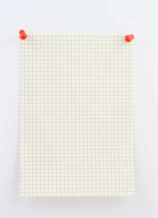 memorise: piece of squared paper pinned to a white wall with red pins Stock Photo