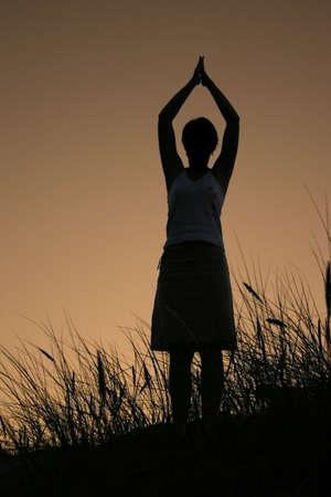 murk: female silhouette celebrating summer sunset, PERSON ISNT IDENTIFABLE Stock Photo
