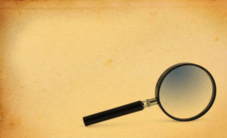 magnifying glass with yellowed paper copy space photo