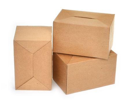 close-up van drie kartonnen dozen tegenover een witte achtergrond, minimale natuurlijke schaduw in front