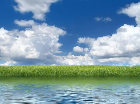 mooi meer met groene grassfield op de achtergrond en bewolkte hemel boven Stockfoto