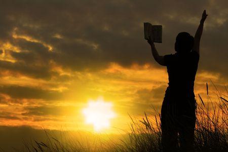 vrouwen bidden met de bijbel tegen de zomer zonsondergang, persoon niet identifable Stockfoto