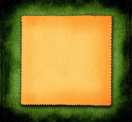 scabrous: piece of yellowed paper against green material background