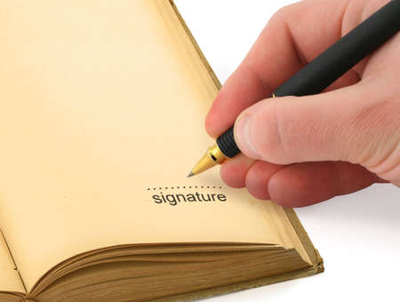 autograph: hand writing a signature in a book