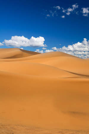 erg: sand dunes and cumulus clouds over them, Erg Chebbi, Morocco  Stock Photo