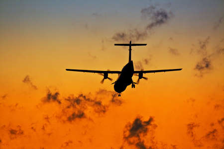 Sunset scene with silhouette of a landing plane photo