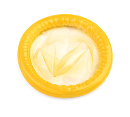 close-up of a yellow condom on white background Stock Photo