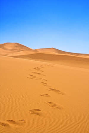 footsteps on sand dunes, cloudless sky in background, focus set in foreground Stock Photo - 5913793