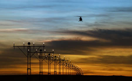 continuation: runway lights and silhouette of a helicopter againts summer sunset sky Stock Photo