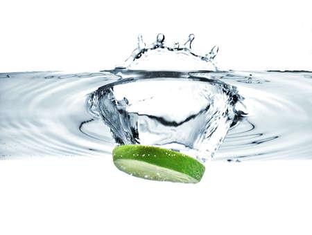 lime slice falling into water making a splash Stockfoto
