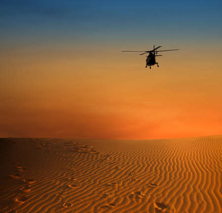 sunset scene with silhouette of a helicopter over dersert