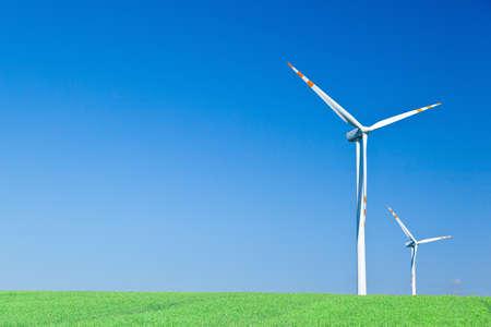 two wind turbines on green field photo