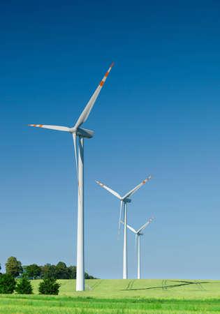 three wind turbines on green field, cloudless sky behind photo