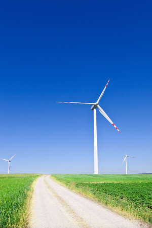 three wind turbines and empty country road photo