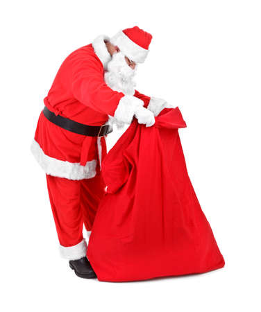 Santa Claus is looking for gifts on white background photo