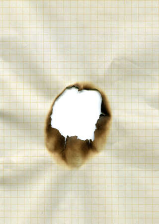 burnt out hole in piece of squared paper photo