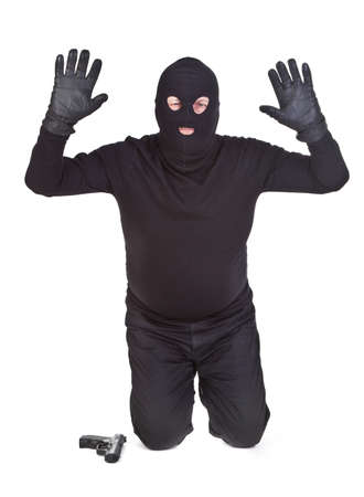 balaclava: bandit kneeling and surrendering on white background