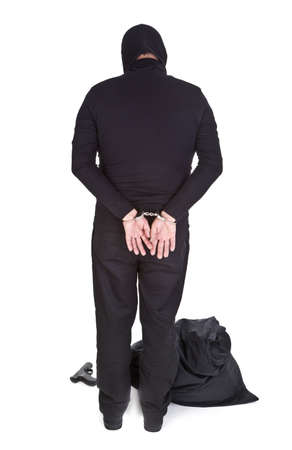 object oppression: thief handcuffed isolated on white background, view from behind Stock Photo