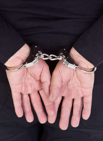 object oppression: close-up of thiefs hands in handcuffs