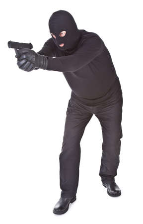 robber aiming with his gun isolated on white background Stock Photo - 9374304