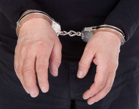 close up of thiefs hands in handcuffs photo