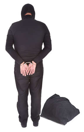 object oppression: thief with sack handcuffed on white background, view from behind Stock Photo