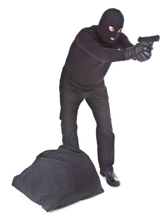 robber with sack aiming with his gun isolated on white background photo