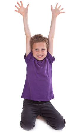 happy young boy with hands raised against white background