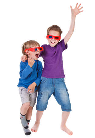 two boys having fun wearing 3D glasses on white background photo