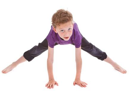 gymnastique: Litte gar�on essaie de faire de colonne vert�brale sur fond blanc