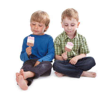 messily: two little boys eating ice lolly on white background messily Stock Photo