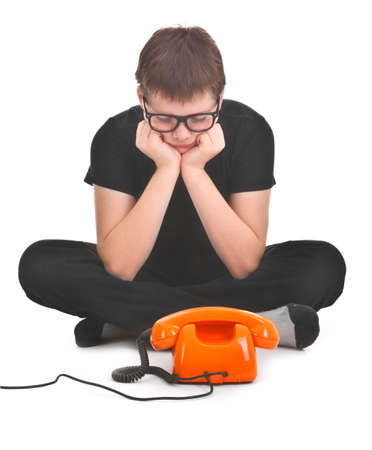 phonecall: sad boy is waiting for expected phonecall over white background
