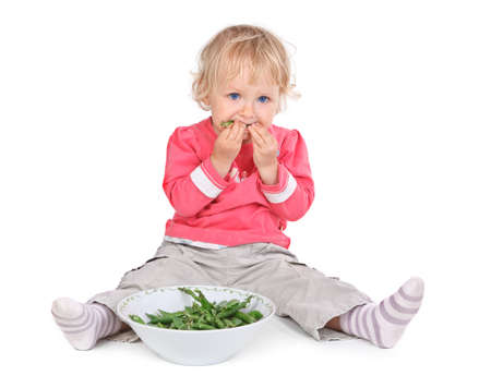 small girl eating grean peas on white background Stock Photo - 16671947