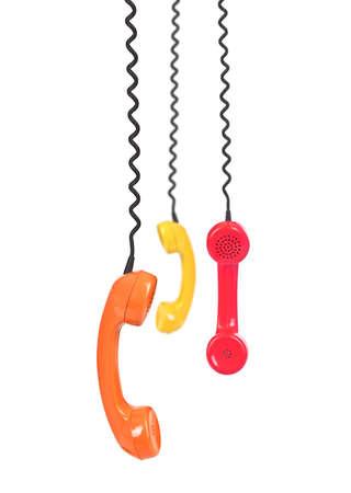 group of telephone receivers isolated on white background, focus set on the orange one Stockfoto