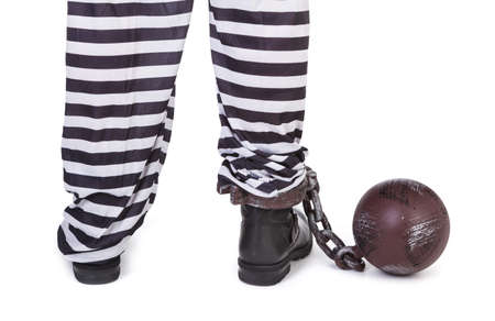 indebted: prisoners legs and ball and chain on white, view from behind